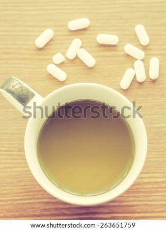 Cup of coffee with medicine pills, Vintage style filter - stock photo
