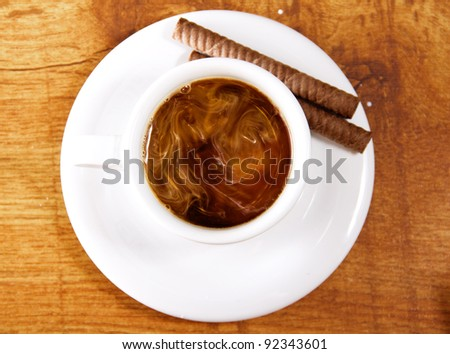 Cup of coffee with milk and cookies on wooden table - stock photo