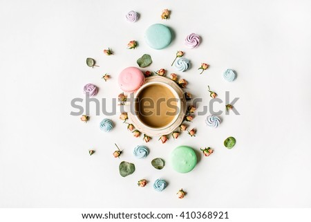 Cup of coffee with milk and macarons on white background. Flat lay, top view - stock photo