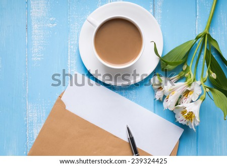 Cup of coffee with milk, blank paper in the envelope, pen and alstroemeria flowers on the blue colored wooden table, top view - stock photo
