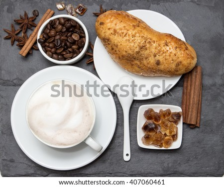 Cup of coffee with milk foam and biscuits and coffee beans lying on a black stone stand, top view. Delicious breakfast with a nice cup of coffee and desert for morning day. Original and real food.  - stock photo