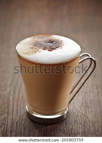 cup of coffee with milk on brown wooden table - stock photo