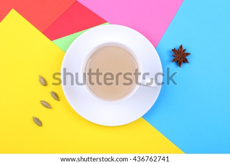 Cup of coffee with milk on saucer on the multicolored paper napkin on the table. Concept of art, artistic professions and coffee break. - stock photo