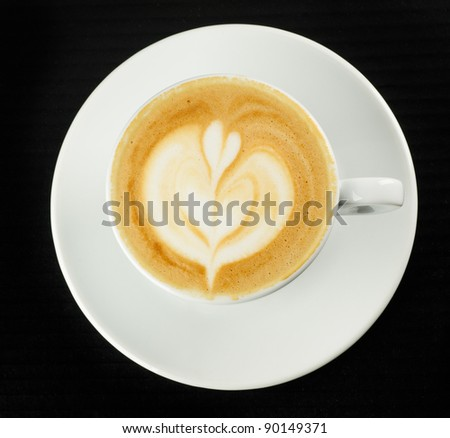 Cup of coffee with milk pattern on black table - stock photo