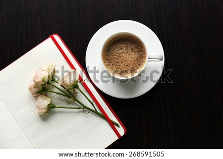 Cup of coffee with notebook and fresh flower on wooden table background - stock photo