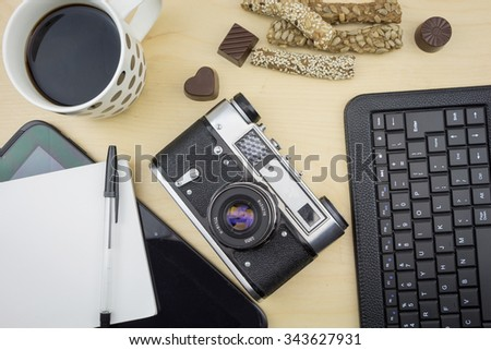 Cup of coffee with notepad, old camera and keyboard on wooden surface. - stock photo