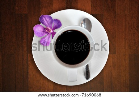 Cup Of Coffee With Orchids on wooden table - stock photo
