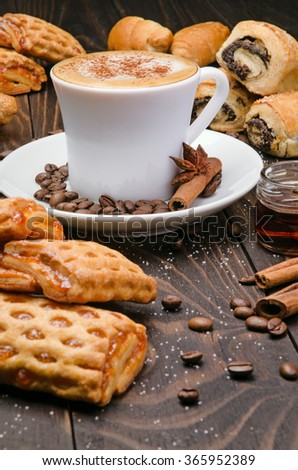 Cup of Coffee with Pastry on brown wood table background