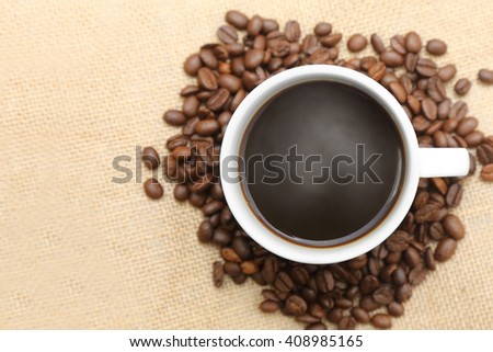 cup of coffee with roasted coffee on burlap sack - stock photo