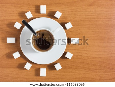 Cup of coffee with saucer and sugar like a clock on a wooden brown table, top view - stock photo