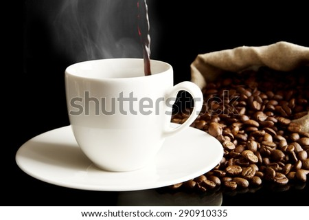 Cup of coffee with saucer with bag with coffee beans isolated on black - stock photo