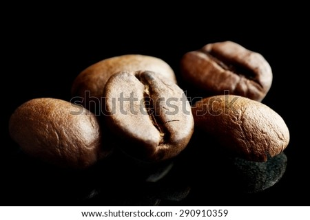 Cup of coffee with saucer with bag with coffee beans isolated on black