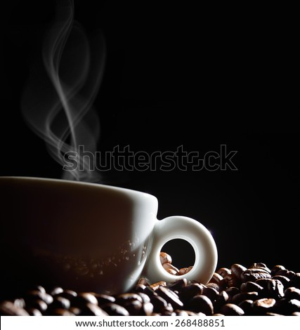 Cup of coffee with smoke and coffee beans on black background - stock photo