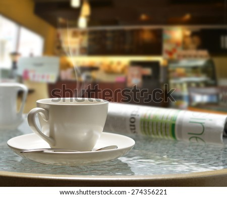 Cup of coffee with smoke and newspaper in coffee shop - stock photo