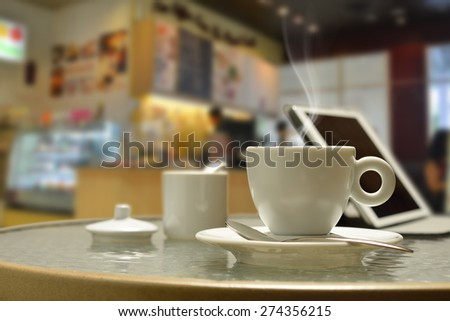 Cup of coffee with smoke and tablet computer in coffee shop - stock photo