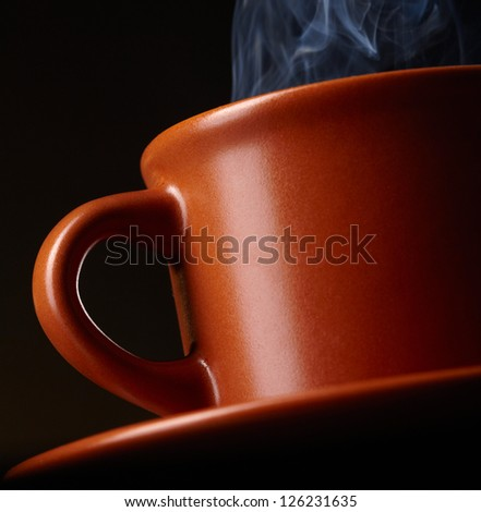 Cup of coffee with smoke over dark background - stock photo