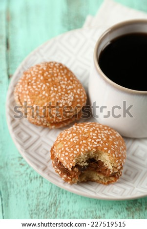 Cup of coffee with tasty cookie on color wooden background - stock photo