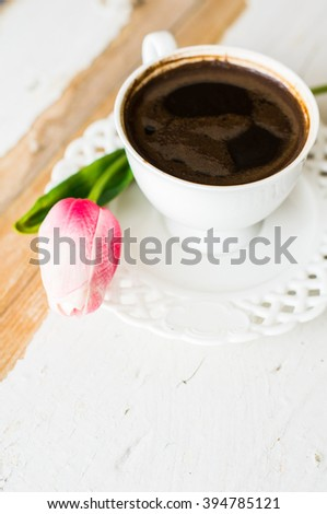 Cup of coffee with tulip flowers on rusty background