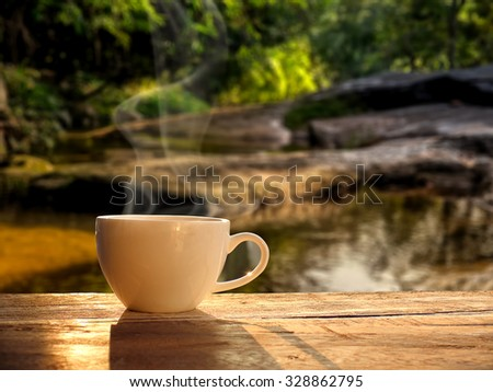 cup of coffee with water fall at morning sunrise.