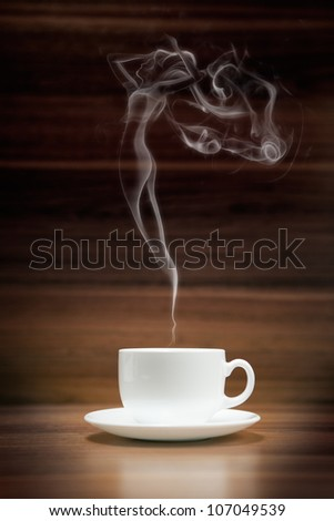 Cup of coffee with woman-shaped smoke on dark wood background - stock photo