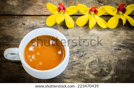 cup of coffee with yellow orchid on old wood background - stock photo