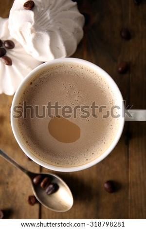 Cup of coffee with zephyr and beans on wooden table, top view - stock photo