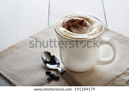Cup of delicious frothy cappuccino sprinkled with chocolate or cacao powder for an aromatic energising drink - stock photo