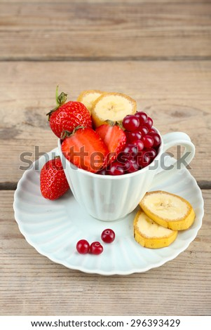 Cup of dessert with fresh fruits on wooden table, closeup - stock photo
