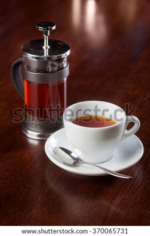 Cup of drink and french press on wooden table in coffeeshop. Shallow dof. - stock photo