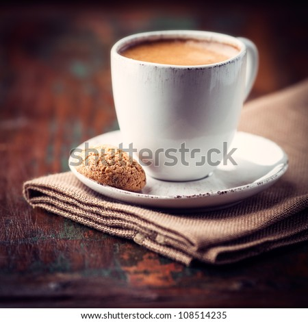 Cup of espresso and biscotti (focus on the biscotti) - stock photo