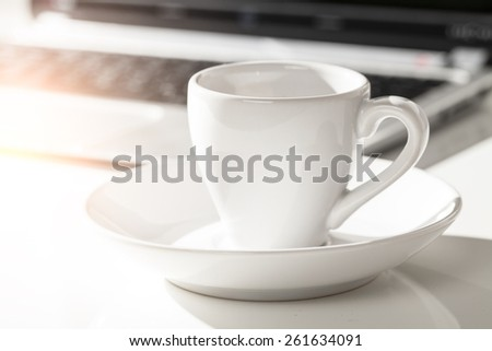 cup of espresso and laptop on desk - stock photo