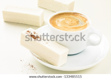 Cup of espresso and sweat candies on white table - stock photo