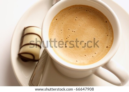 Cup of espresso coffee and chocolate candies - stock photo