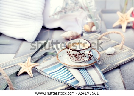 Cup of espresso served on vintage wooden tray, with marine style decorations. Natural light toned photo, with cushions and decorations on the background. - stock photo