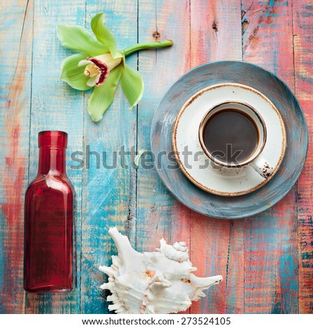 Cup of espresso set with an orchid flower and seashells, on brightly colored wooden background. Holiday by tropical sea relaxation concept.  - stock photo