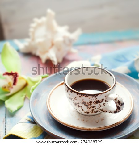 Cup of espresso set with an orchid flower and seashells, on brightly colored wooden background. Holiday by tropical sea concept. - stock photo