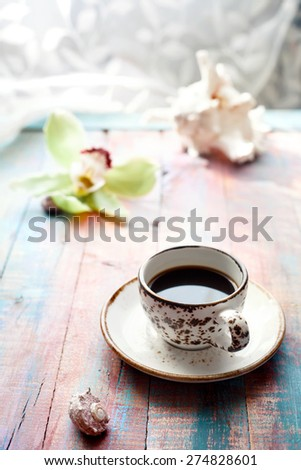 Cup of espresso set with an orchid flower and seashells, on brightly colored wooden background. Holiday by tropical sea relaxation concept. Shallow focus. Toned photo. - stock photo