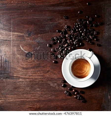 Cup of Espresso with Dark Coffee Beans; seen from above