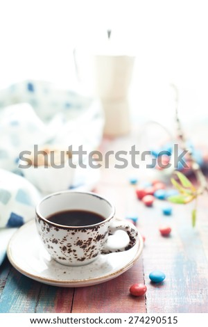 Cup of espresso with red and blue sweets on brightly colored wooden table, set with cane sugar and tree branch with fresh spring leaves. Shallow focus, natural light. Toned photo. - stock photo