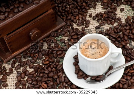 Cup of Expresso Coffee with old grinder and coffee beans. - stock photo