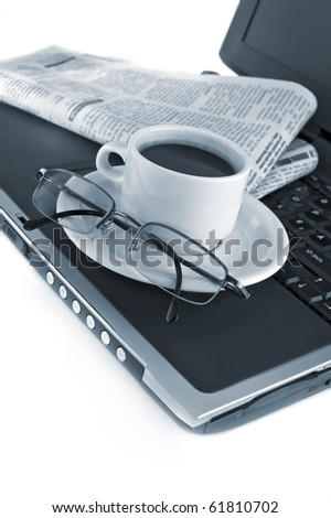 Cup of fragrant coffee on a laptop and morning paper business news - stock photo
