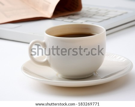 Cup of fragrant coffee on a morning paper - stock photo