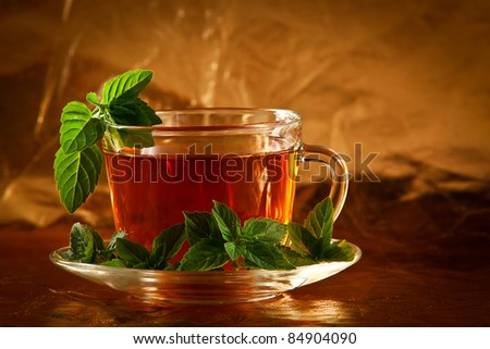 Cup of fragrant tea with fresh leaves of green tea - stock photo