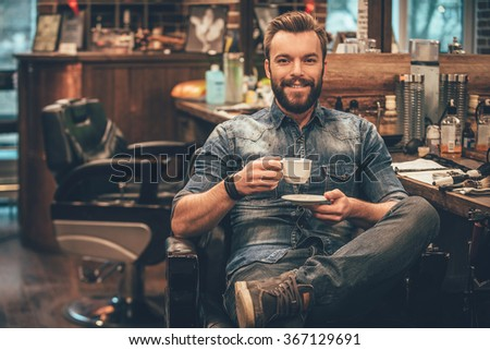 Cup of fresh coffee at barbershop. Cheerful young bearded man looking at camera and holding coffee cup while sitting in chair at barbershop - stock photo