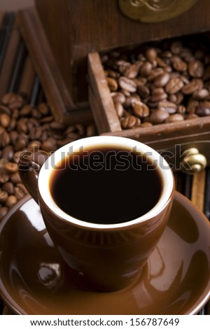 Cup of fresh coffee with vintage coffee grinder - stock photo