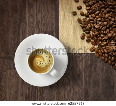 Cup of fresh espresso and roasted coffee beans on dark wooden background - stock photo