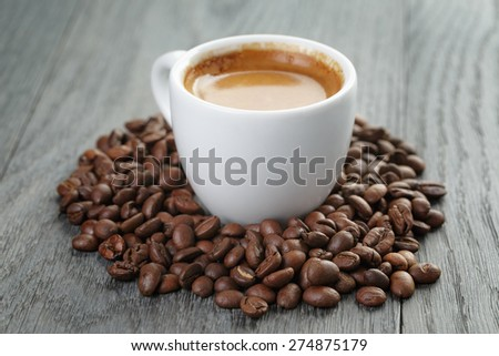 cup of fresh espresso with coffee beans on oak table