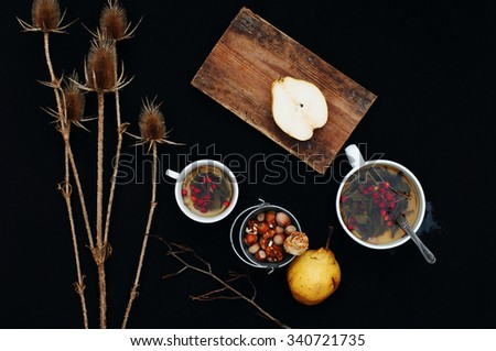 Cup of fresh herbal tea on black table. Cup of green herbal tea. Herbal tea. Sliced pear on a chopping board. Ripe fresh organic yellow pears on black  background. Nuts. Botanical. Dry plant. Top view - stock photo