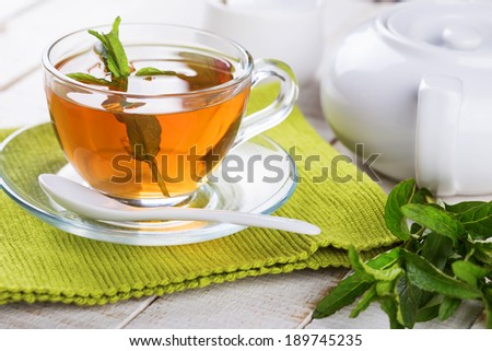 Cup of fresh herbal tea on wooden table. Selective focus, horizontal. - stock photo