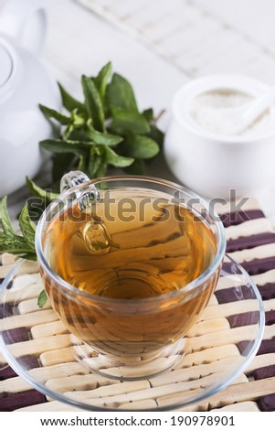 Cup of fresh herbal tea on wooden table. Selective focus, vertical.